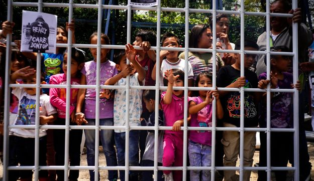 Children hold up a metal fence to symbolize detained immigrant children outside the U.S. embassy in Mexico City, Tuesday, June 26, 2018.