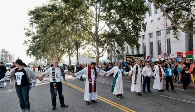 Members of a group of clergy hold hands and sing in the middle of the street during a civil disobedience protest in front of Federal Courthouse in Los Angeles on Tuesday, June 26, 2018.