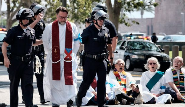 A  clergy member is arrested during a civil disobedience protest in front of Federal Courthouse in Los Angeles on Tuesday, June 26, 2018.