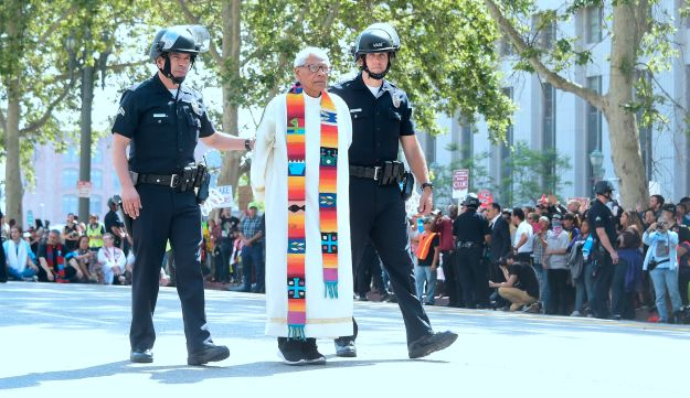 Members of the clergy from different denominations, including Father Richard Estrada (C), are arrested in an act of civil disobedience in Los Angeles, California on June 26, 2018.