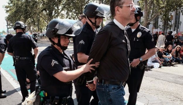 A member of clergy group is arrested during a protest in front of Federal Courthouse in Los Angeles on Tuesday, June 26, 2018.