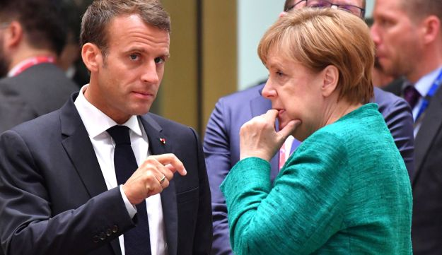 French President Emmanuel Macron, left, speaks with German Chancellor Angela Merkel during a round table meeting at an EU summit in Brussels, Thursday, June 28, 2018. European Union leaders meet for a two-day summit to address the political crisis over migration and discuss how to proceed on the Brexit negotiations. (AP Photo/Geert Vanden Wijngaert)