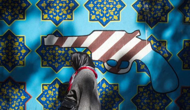An Iranian woman walks past an anti-U.S. mural on the wall of the former U.S. embassy in Tehran October 12, 2011