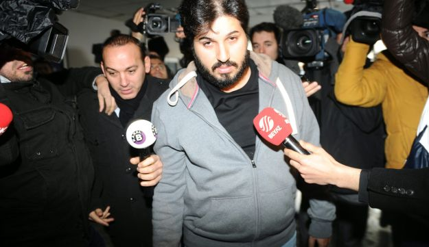 Detained Azerbaijani businessman Reza Zarrab (C) is surrounded by journalists as he arrives at a police center in Istanbul on December 17 ,2013