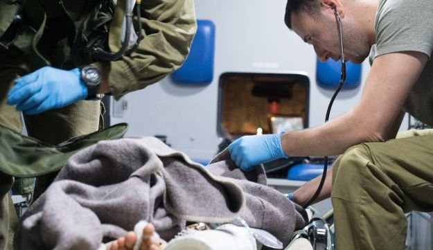 Soldiers treat a wounded child who arrived at the border on Friday.
