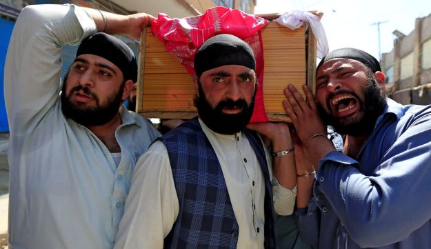 Afghan Sikh men carry the coffin of one of the victims in Jalalabad city, Afghanistan July 2, 2018.