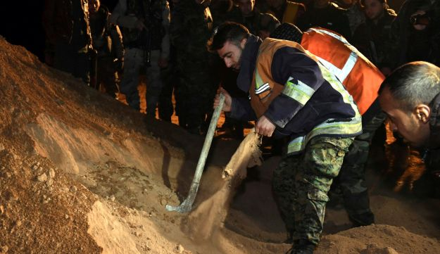 A Syrian security force member checks human remains at the site where two mass graves were discovered.