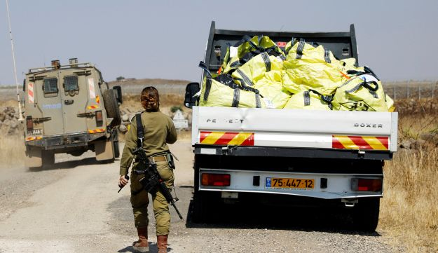 An Israeli soldier walks next to a truck loaded with donations collected in the Golan Heights before they are delivered over the border to Syria, July 5, 2018.
