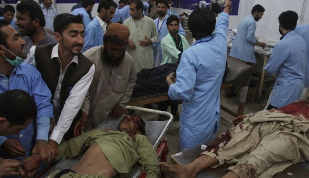 Hospital staff treat people injured in a bomb blast, at a hospital in Quetta, Pakistan, Friday, July 13, 2018