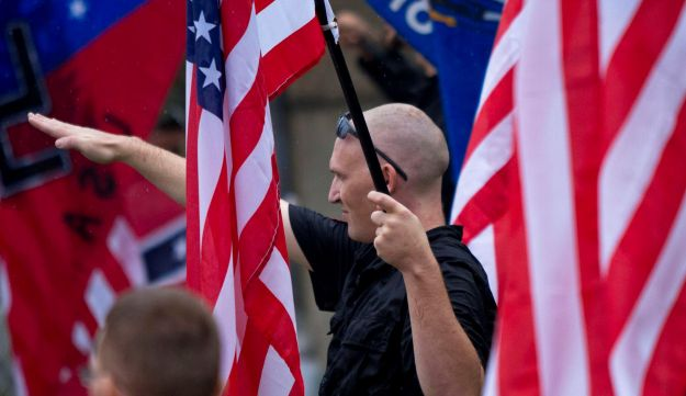 A member of a white supremacy group gives the fascist salute during a gathering in Wisconsin on September 3, 2011.