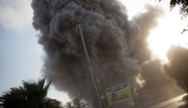Smoke raises in the background following an Israeli airstrike hits a governmental building in Gaza City , Saturday, July 14, 2018