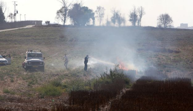 Firemen extinguish fires caused by burning kites sent from Gaza over the weekend at Nahal Oz