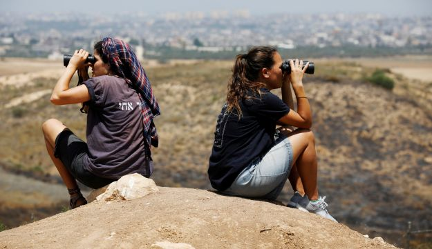 Israeli women look into binoculars as they scan the area for incoming kites and balloons carrying flammable materials on the Israeli side of the border between Israel and Gaza June 8, 2018. REUTERS/Amir Cohen