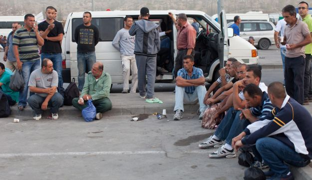 Palestinian workers at Tarqumiya crossing on their way to Israel, 2013.