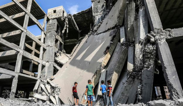 Palestinian boys walk through the wreckage of a building that was damaged by Israeli air strikes in Gaza City on July 15, 2018