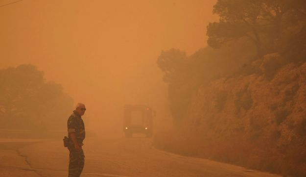 Smoke fills the sky as a member of the emergency services blocks a road near Kineta, west of Athens, Monday, July 23, 2018.
