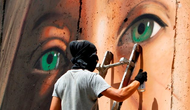 Italian artist Jorit Agoch paints a mural depicting jailed Palestinian teenager Ahed Tamimi on Israel's controversial separation barrier in the West Bank city of Bethlehem, on July 25,2018.