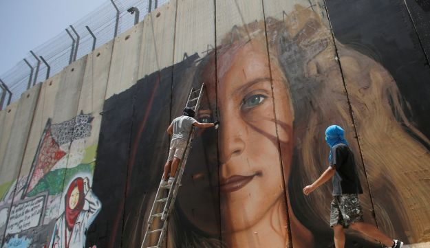 An artist paints a mural depicting Palestinian teen Ahed Tamimi, Bethlehem, West Bank July 25, 2018.