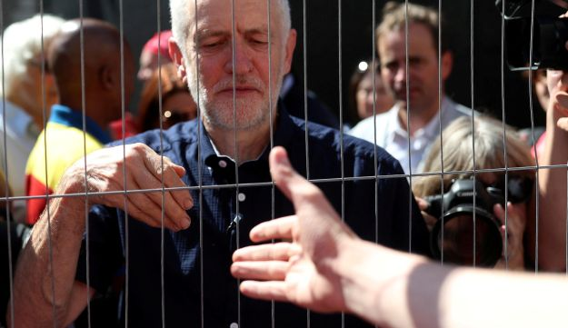 British Labour Party leader Jeremy Corbyn trying to shake hands with a supporter following a march in central London, June 30, 2018.