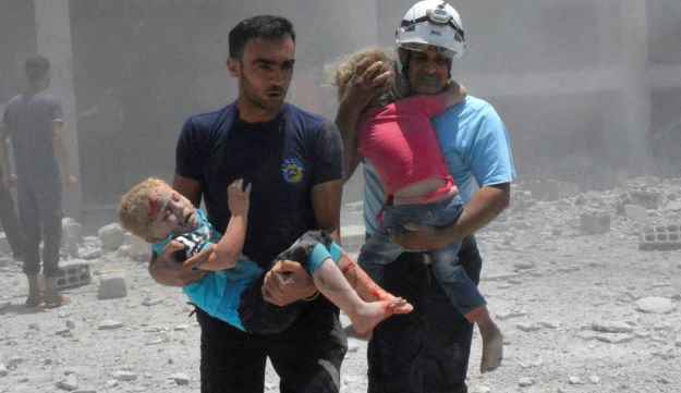 Photo provided by the Syrian Civil Defense: White Helmets carrying children after airstrikes hit a school housing displaced people, in the southern Daraa province of Syria. June 14, 2017