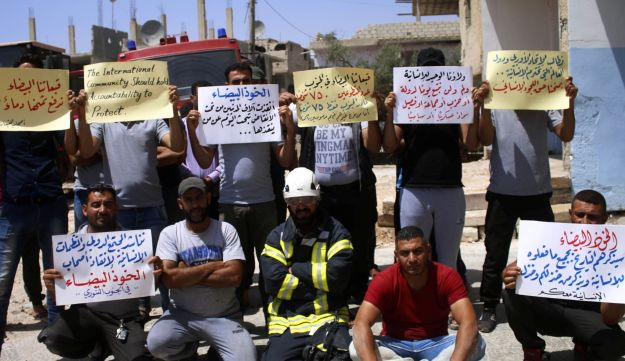 Trapped White Helmet rescue workers hold up signs urging the international community to help evacuate them from conflict areas during a sit-in in the southern Syrian city of Daraa on July 24, 2018