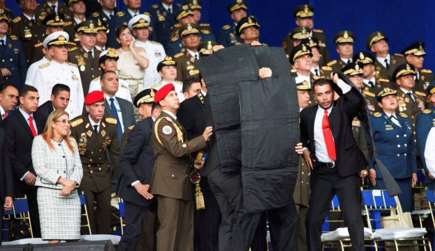 Security personnel surround Venezuela's President Nicolas Maduro during an incident as he was giving a speech in Caracas, Venezuela, August 4, 2018
