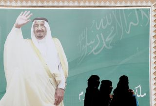 Women walk past a poster of Saudi Arabia's King Salman bin Abdulaziz Al Saud on the outskirts of Riyadh, Saudi Arabia. February 12, 2018
