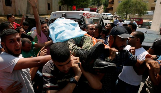 People carry the body of a Palestinian Hamas militant who was killed in Israeli tank shelling, at a hospital in the northern Gaza Strip, August 7, 2018.