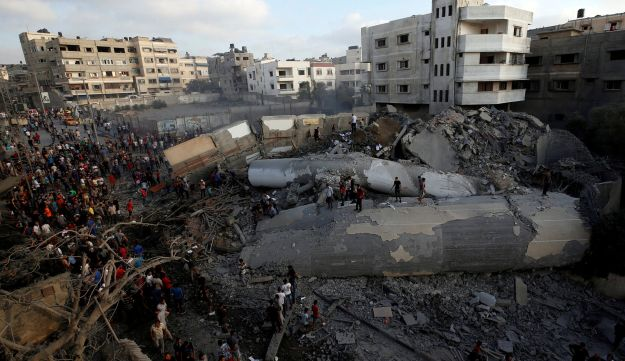 Palestinians gather around a building after it was bombed by an Israeli aircraft, in Gaza City August 9, 2018