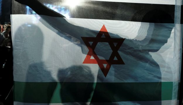 A protester holds up a version of the Israeli flag that uses the colors of the Palestinian flag in Tel Aviv on August 11, 2018.