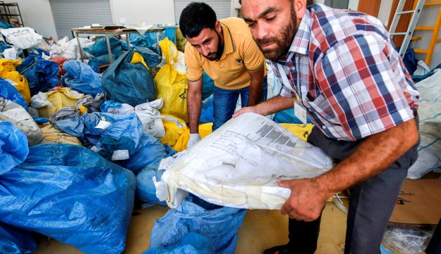 Palestinian postal workers sift through sacks of previously undelivered mail dating as far back as 2010, Jericho, West Bank, August 14, 2018.
