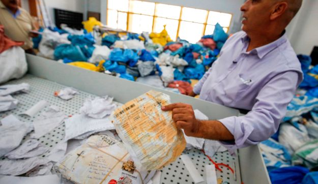 Ramadan Ghazawi, a Palestinian official at the central international exchange post office in the West Bank city of Jericho, holds a bill for a letter, West Bank, August 14, 2018.