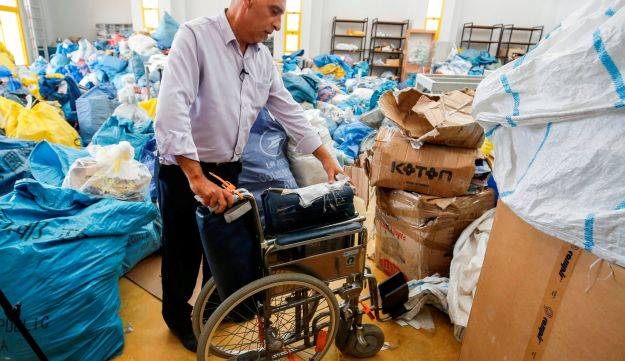 Ramadan Ghazawi, a Palestinian official at the central international exchange post office in the West Bank city of Jericho, stands next to a folded wheelchair, August 14, 2018.