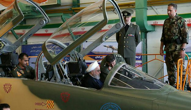Handout picture released by the Iranian Presidency on August 21, 2018, shows President Hassan Rouhani  sitting in the cockpit of a fourth-generation fighter with 'advanced avionics.'