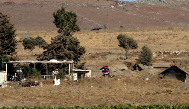 Uniformed men chat on the Syrian side of the ceasefire line between Israel and Syria, as seen from the Israeli-occupied Golan Heights, July 26, 2018.