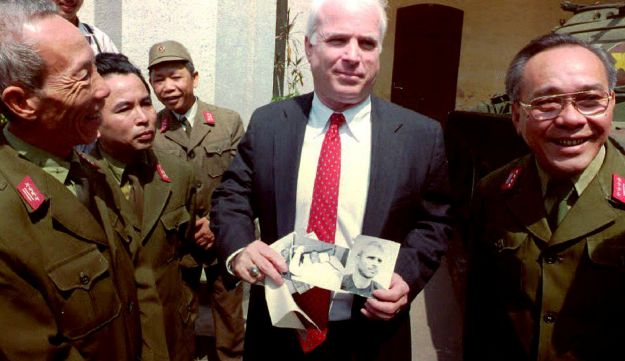 John McCain holds up photos of himself as a 30-year-old man wounded and captured in 1967 in North Vietnam, Hanoi, 19 October, 1992.