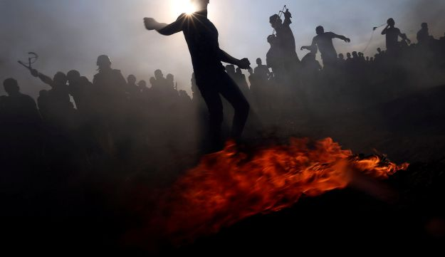 Palestinian demonstrators hurl stones at Israeli troops during a protest demanding the right to return to their homeland, at the border fence between Israel and Gaza, in the southern Gaza Strip August 24, 2018.