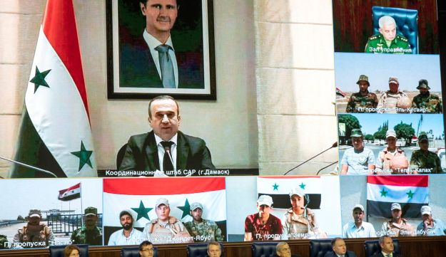 A portrait of Syrian President Bashar Assad is displayed on the screen as participants attend a video call between Moscow and Syria, Moscow, Russia, August 30, 2018.