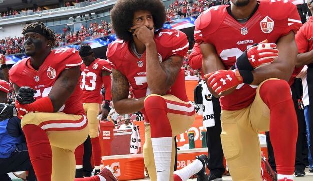 In this file photo taken on October 02, 2016 (L-R) Eli Harold #58, Colin Kaepernick #7 and Eric Reid #35 of the San Francisco 49ers kneel on the sideline during the anthem prior to the game against the Dallas Cowboys at Levi's Stadium in Santa Clara, California