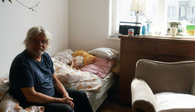 Wojciech Danko sits on the bed while his mother, Krystyna, 101, rests in their Warsaw apartment, September 6, 2018.