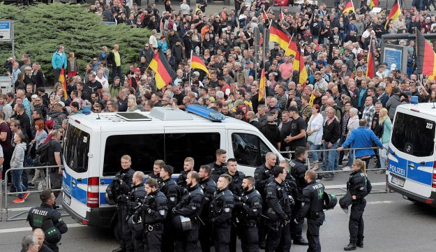 People are watched by police as they attend a demonstration in Chemnitz, eastern Germany, Friday, September 7, 2018