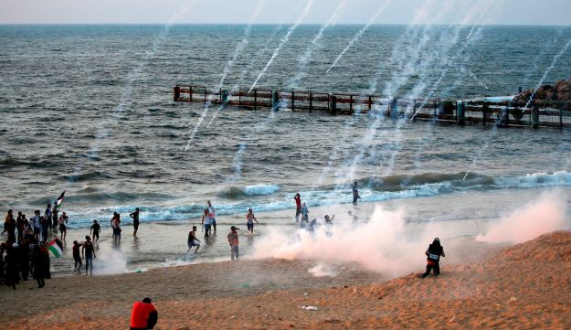 Trails of smoke from tear gas canisters fired by Israeli forces are seen as Palestinians protest on the beach near the maritime border with Israel, in the northern Gaza Strip, calling for the lift of the Israeli blockade on the coastal Palestinian enclave, on September 10, 2018.