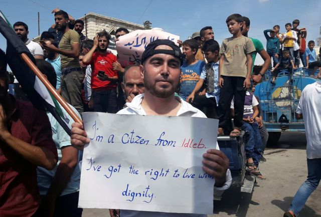 Protester holds a placard, in Harim, a town in Idlib province, Syria, Sept 7, 2018.