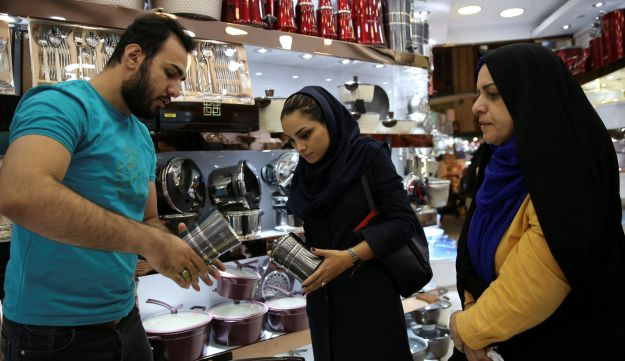A salesclerk shows off his goods to Kiana Ismaili, 26, as she shops with her mother at the Grand Bazaar in Tehran, Iran, September 6, 2018