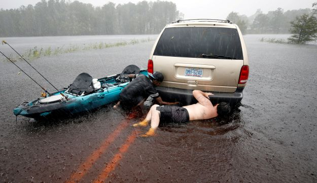 Two men try to free a stalled car that became stranded in rising flood waters after Hurricane Florence struck in Boiling Spring Lakes, North Carolina, U.S., September 15, 2018.