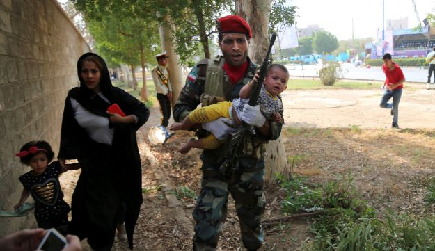 Iranian army member carries away a child from a shooting scene in the southwestern city of Ahvaz, Iran, September 22, 2018