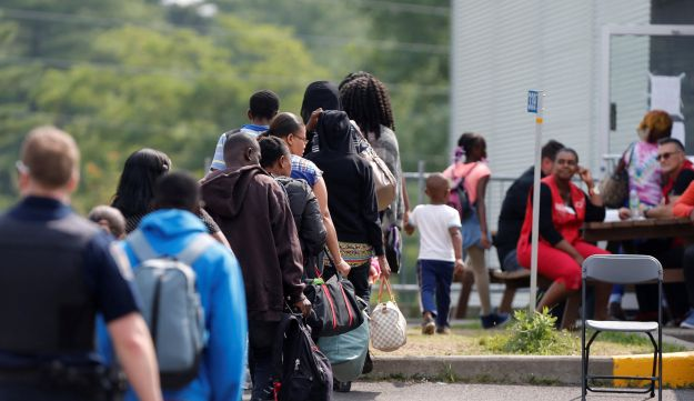 A group of asylum seekers wait to be processed after being escorted from their tent encampment to the Canada Border Services in Lacolle, Quebec, Canada August 11, 2017.