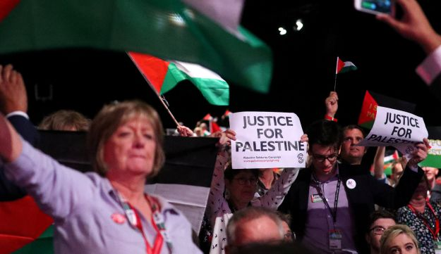 Delegates hold up placards in support of Palestine at the Labour Party's conference in Liverpool, Britain, September 25, 2018