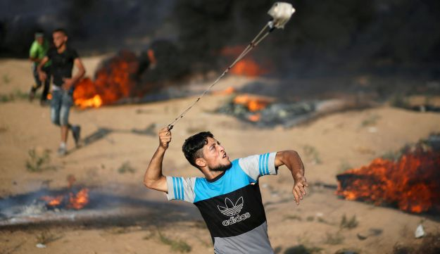 A Palestinian hurls stones at Israeli troops during a protest calling along the Israel-Gaza border fence east of Gaza City, September 28, 2018.