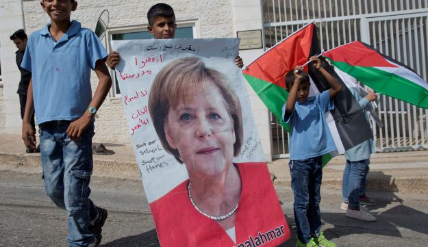 Bedouin children from Khan al-Ahmar holds posters of German Chancellor Angela Merkel and Palestinian flags in front of the German representative office, Ramallah, West Bank, October 3, 2018.
